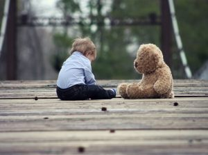 boy sitting alone with teddy bear